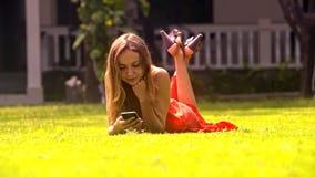 Flickan ligger på gräs som pratar med vänner parkerar in lager videofilmer