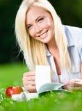 Flickan ligger på grönt gräs och läser boken arkivfoto