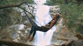 Flickan ligger på hängmattan mot den bildmässiga vattenfallet
