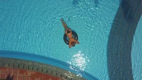 Flickan ligger på livboj i simbassäng och kopplar av stock video