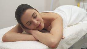 Flickan ligger på massagetabellen royaltyfri bild
