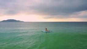 Flickan ligger på paddleboard på magebenägenhet mot händer stock video
