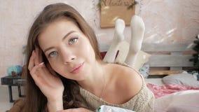 Flickan ligger på sängen på bakgrunden av julgranen nytt år arkivfilmer