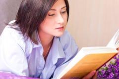 Flickan ligger på en säng och läste boken Arkivfoto
