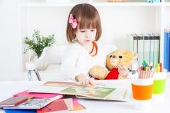 Flickan läser en bilderbok till en nallebjörn Fotografering för Bildbyråer