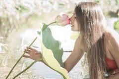 Flickan luktar lotusblomma Arkivfoton