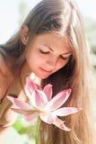 Flickan luktar lotusblomma Royaltyfri Foto
