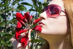 Flickan luktar röda blommor Arkivbilder