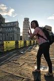 Flickan lyfter hennes hand bredvid det Pisa tornet arkivfoto