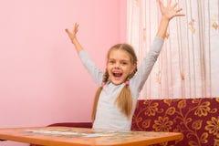 Flickan lyftte lyckligt hans händer som samlar bilden av pussel Arkivbilder