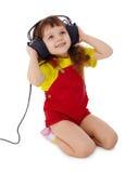 flickan lyssnar little musik till Arkivbild