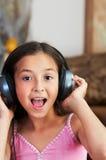 Flickan lyssnar till musik Royaltyfri Bild