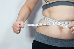 Flickan mäter den fettiga buken Arkivbild