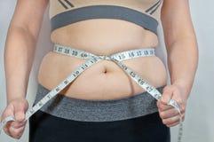 Flickan mäter den fettiga buken Fotografering för Bildbyråer
