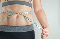 Flickan mäter den fettiga buken Arkivbilder