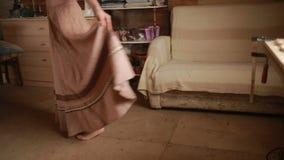 Flickan mäter den långa kjolen som göras av linne stock video