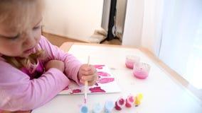 Flickan målar bilden med henne vänstersidahanden i färgmålarfärger lager videofilmer