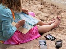 Flickan målar färgpennor för en bild Arkivbild