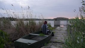 Flickan målar i ett fartyg på solnedgången lager videofilmer