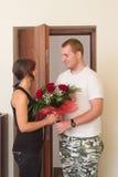 Flickan möter pojkvännen med blommor nära dörren Arkivbilder