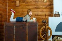 Flickan Masha ligger på den gamla bröstkorgen arkivfoto
