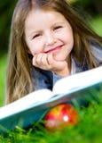 Flickan med äpplet läser boken som ligger på det gröna gräset royaltyfri bild