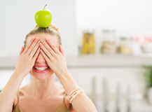 Flickan med äpplet på det head bokslutet synar med händer royaltyfri fotografi
