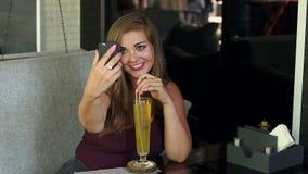 Flickan med överskottvikt sitter i kafé med en telefon stock video