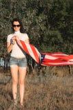 Flickan med amerikanska flaggan utomhus, stjärnor och band sjunker fladdranden i vinden, arkivfoton
