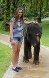 Flickan med behandla som ett barn elefanten Royaltyfri Bild