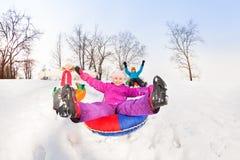 Flickan med ben up, och vänner glider ner kullen Royaltyfri Foto