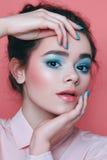 Flickan med blå makeup, med blått spikar på en rosa bakgrund Royaltyfri Fotografi