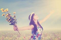 Flickan med blomman tycker om frihet på ängen Royaltyfri Fotografi