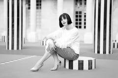 Flickan med brunetthår sitter på gatan avrivna kolonnen Fotografering för Bildbyråer