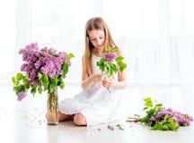 Flickan med buketten av lilan blommar sammanträde på golvet arkivbilder