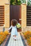 Flickan med buketten lämnar gården Arkivfoton