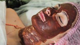 Flickan med chokladmaskeringen som ler med hans ögon, stängde sig tätt med textsidan upp chokladSpa terapi lager videofilmer