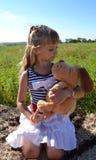 flickan med den mjuka hundleksaken spelar i ängen Arkivbilder