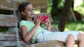 Flickan med den röda smartphonen sitter på gungabänk i trädgården och lyssnar till musik arkivfilmer