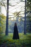 Flickan med den svarta kappan i skogen Royaltyfria Foton
