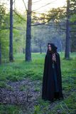 Flickan med den svarta kappan i skogen Arkivbilder