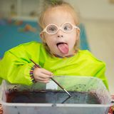 Flickan med Down Syndrome drar modeller i ebruteknik Arkivfoto