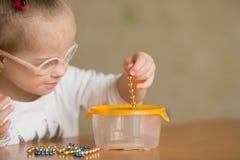 Flickan med Down Syndrome framkallar fint motorisk expertis av händer Arkivfoto