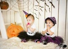 Flickan med Down Syndrome och hennes vän äter godisen på en ferie halloween royaltyfri fotografi