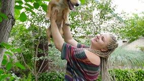 Flickan med dreadlocked håll räcker på en hund HD arkivfilmer