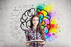 Flickan med en bok och den färgrika hjärnan skissar royaltyfria bilder