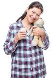 Flickan med en favorit- leksak och ett exponeringsglas av mjölkar royaltyfria foton