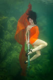 Flickan med en fiol under vatten Royaltyfri Fotografi