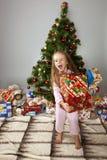 Flickan med en gåva under julgranen Arkivbilder