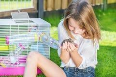 Flickan med en hamster gömma i handflatan in Fotografering för Bildbyråer